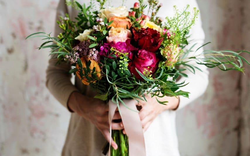 woman-hands-holding-beautiful-flowers-bouquet-PSBRCT6